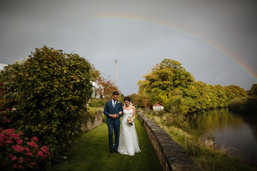 Bride and groom walking underneath a rainbow for a wedding portrait