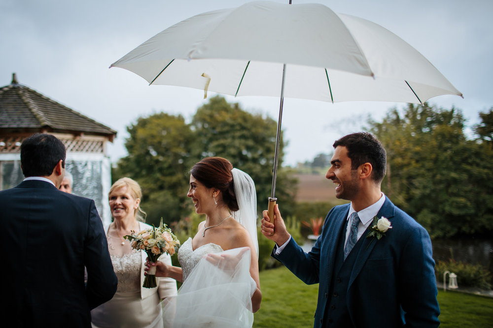 Groom holds an umbrella during a wet wedding in Yorkshire