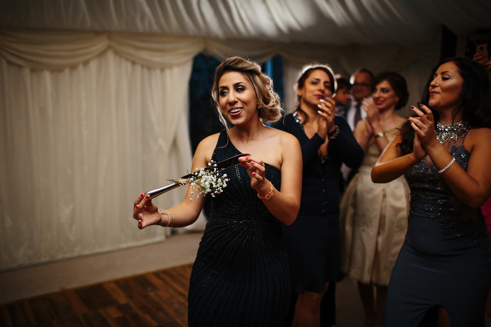 Bridesmaid dancing with the cake knife at a wedding