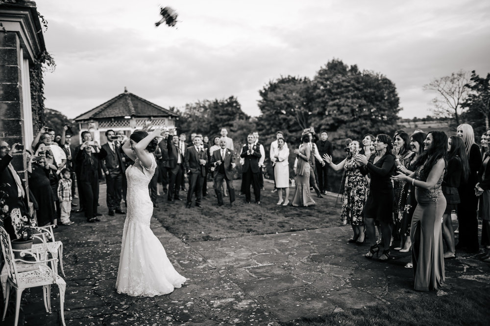 Bride throws the bouquet at a wedding at Tanfield House