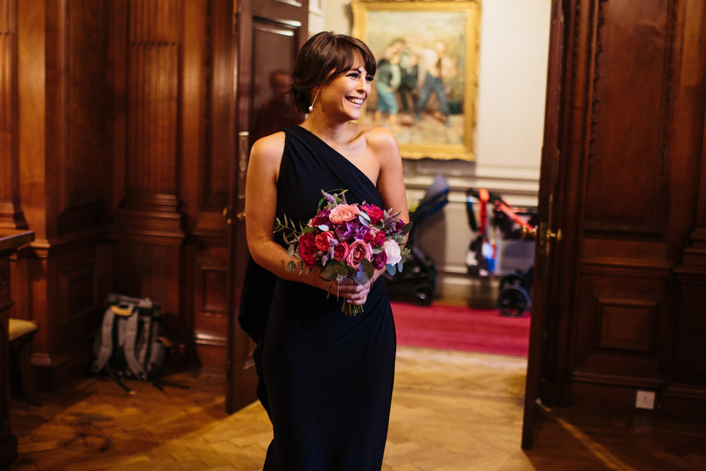 Bride of honour enters wedding reception holding her bouquet
