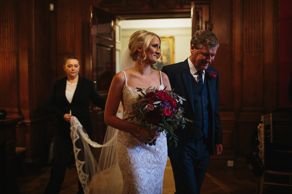 Bride enters her wedding holding her bouquet with her father