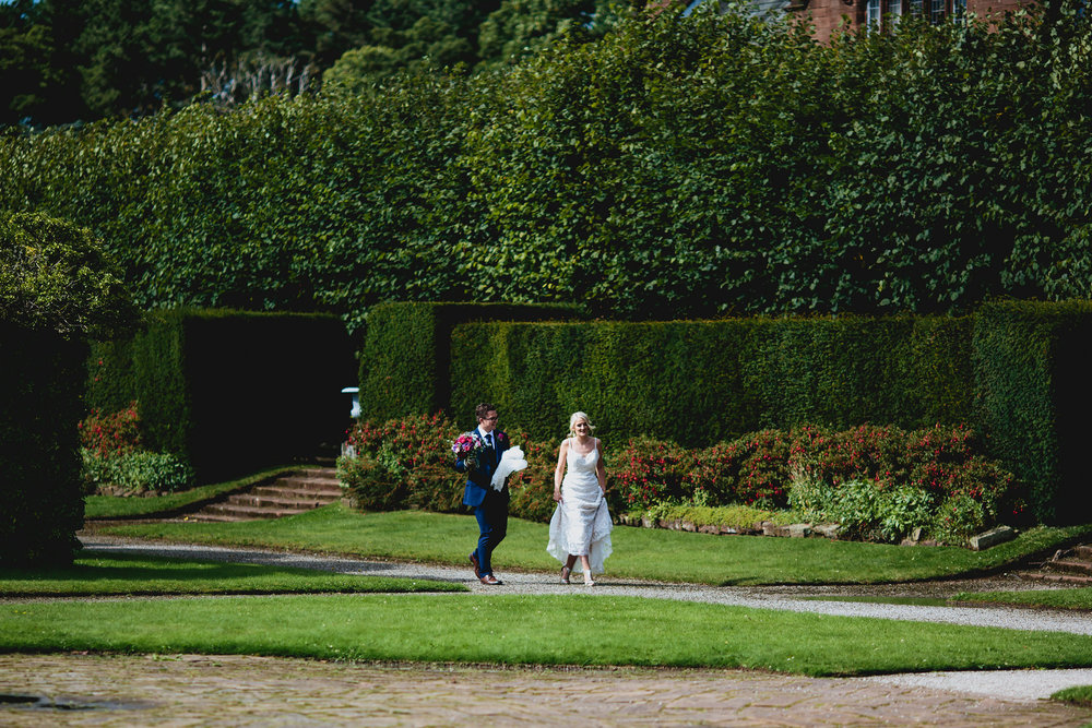 Bride and groom stroll through the gardens at their wedding venue