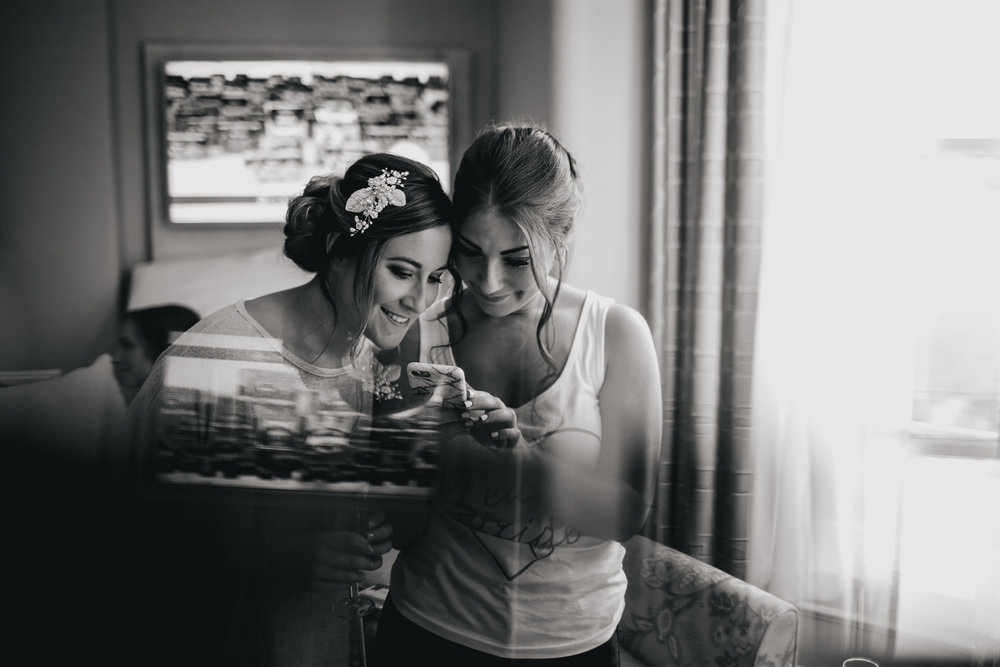 Bride and bridesmaid smiling at a phone on her wedding day
