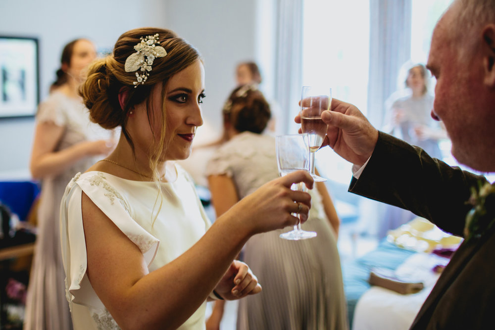 Bride and father share a glass of champagne on her wedding day