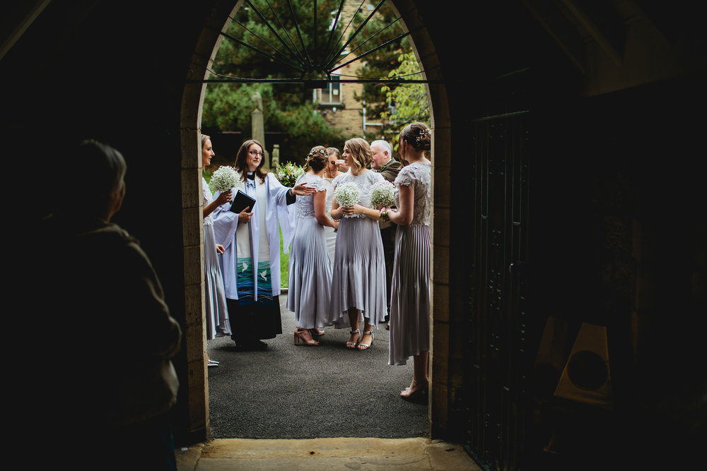 Vicar ushers bridesmaids into the church wedding
