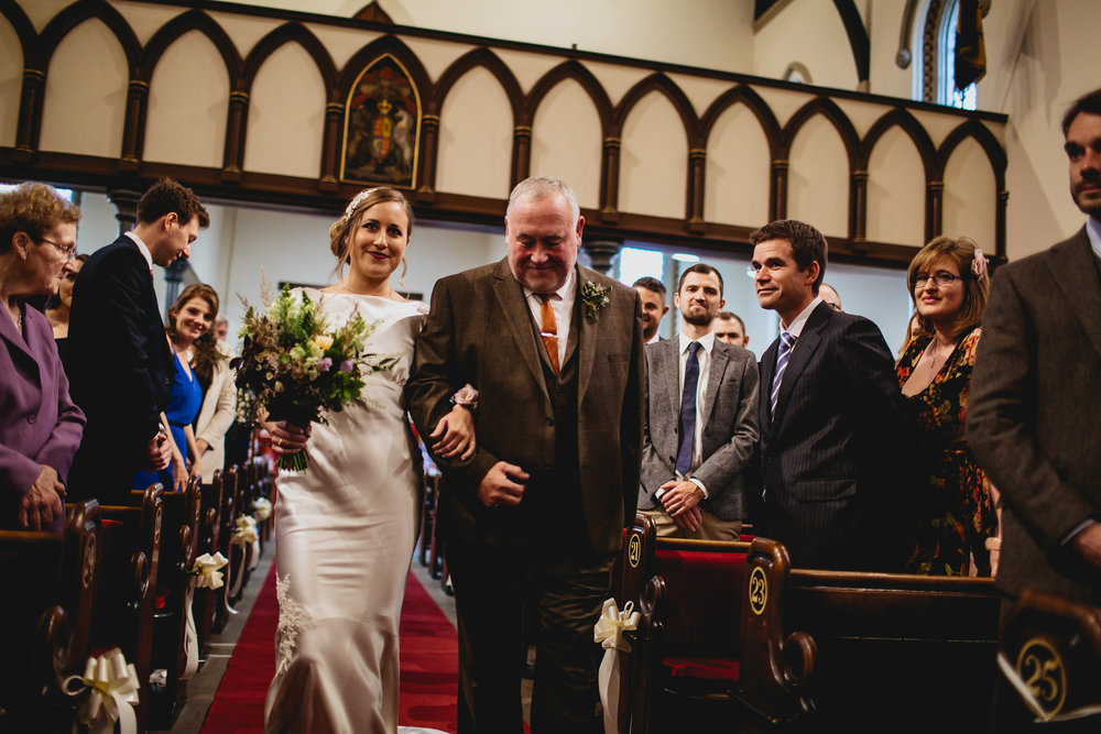Bride and father walk down the aisle at her wedding in Yorkshire