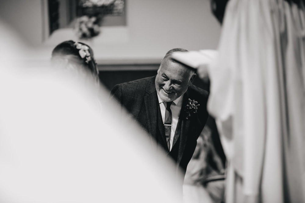 Brides father laughing at a wedding