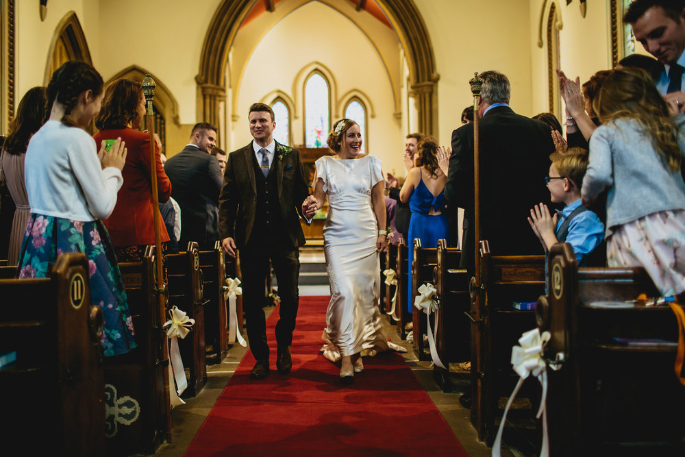 Bride and groom walk down the aisle at their wedding