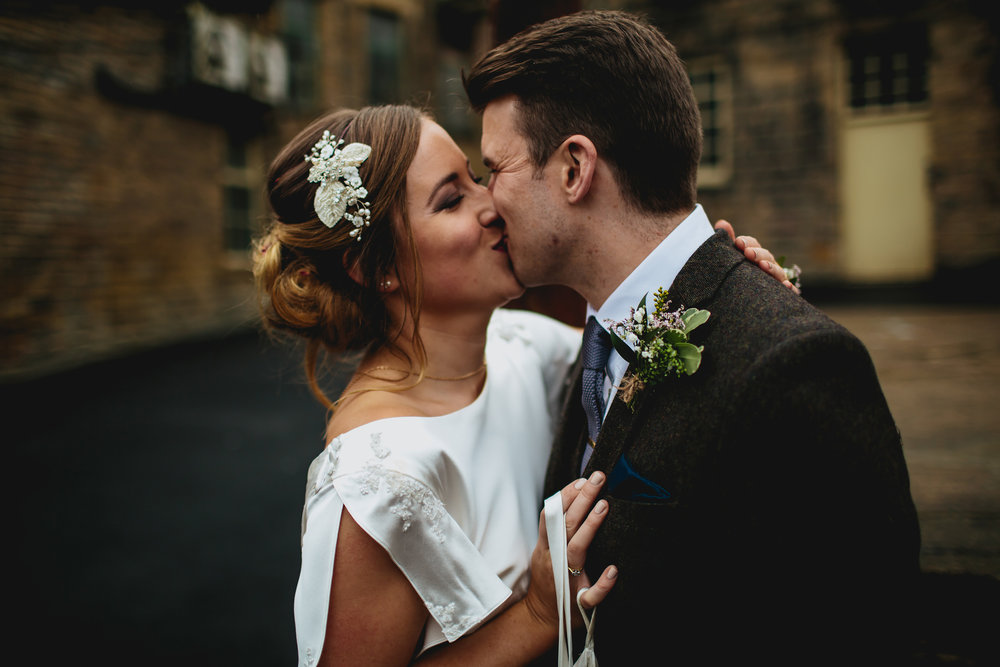 Bride and groom kiss at Sunny Bank Mills Leeds