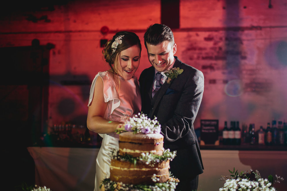 Bride and groom cut the cake at their wedding in Leeds