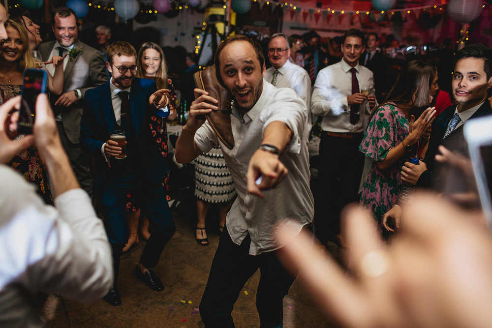 Man dances with shoe at a wedding in Leeds