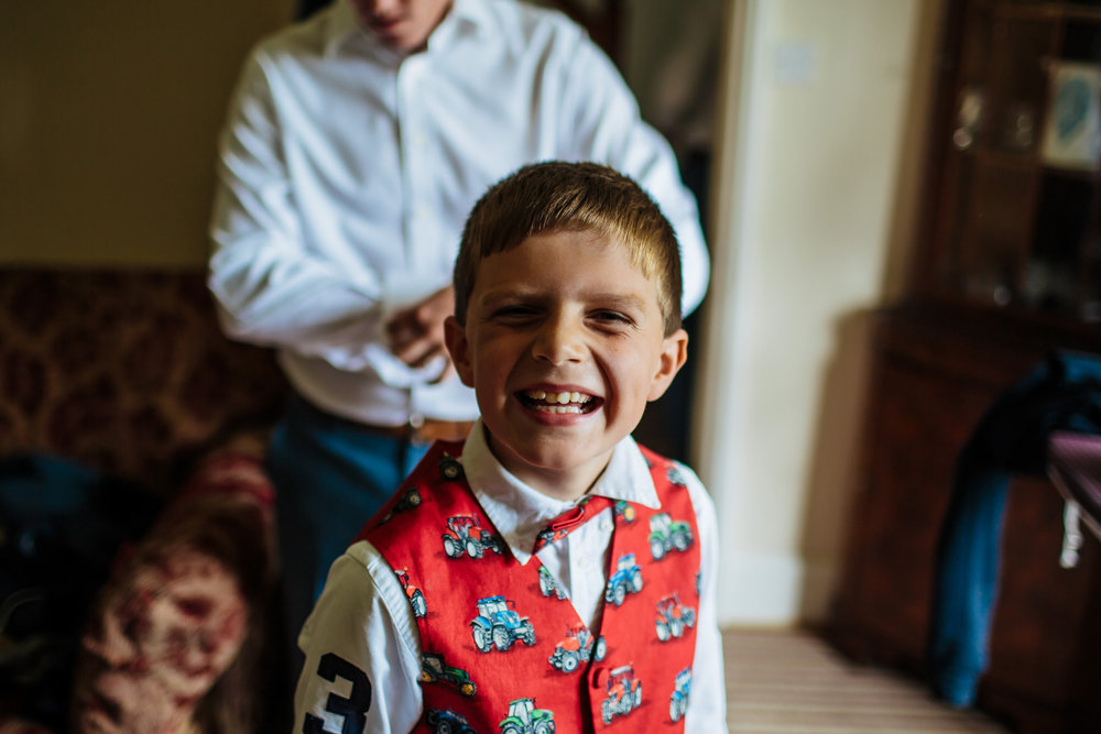 Young boy smiling at the camera before a wedding