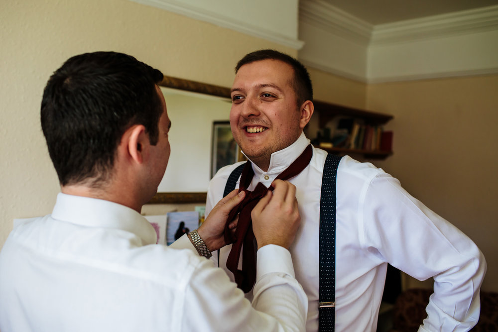 Best man adjusts grooms tie on his wedding day in Lancashire