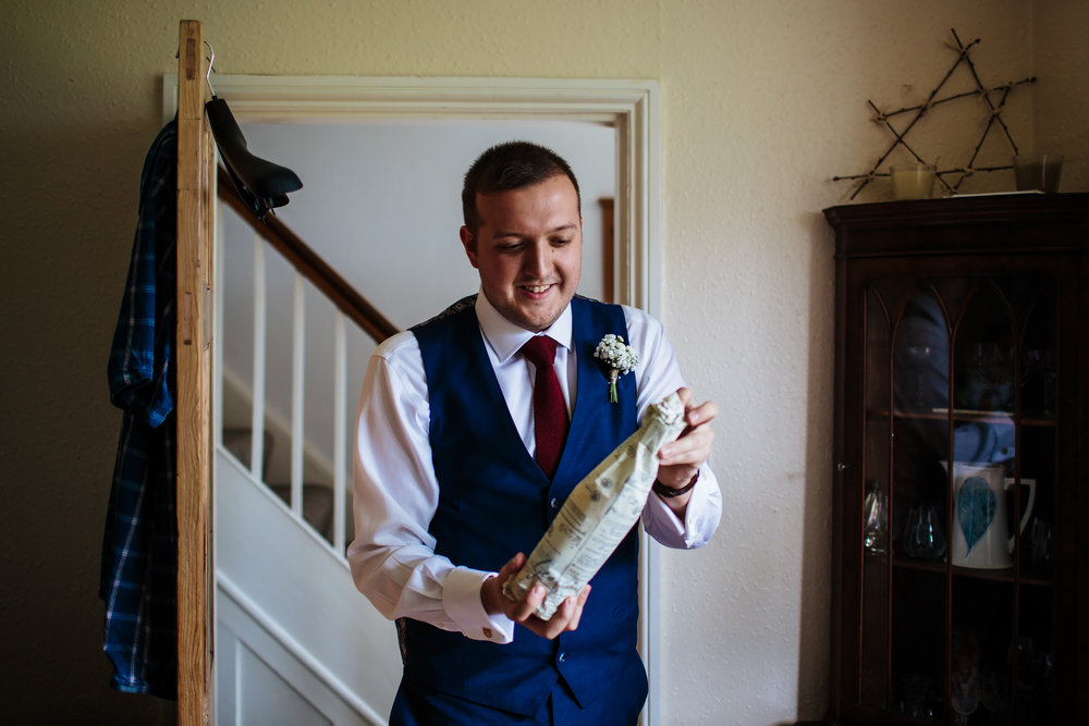 Groom opens a bottle of whisky on his wedding day