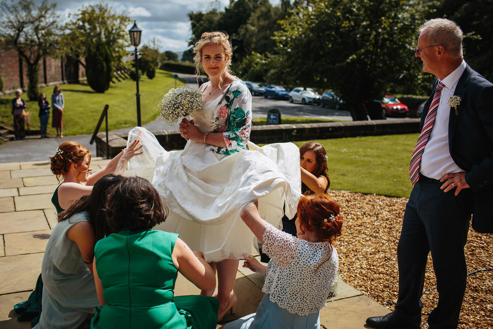 Bridesmaids help the bride with her dress at a wedding