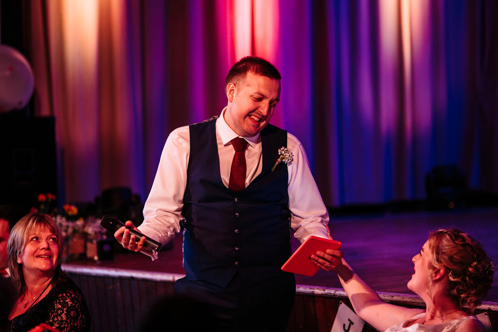 Groom performs his speech at a village hall wedding