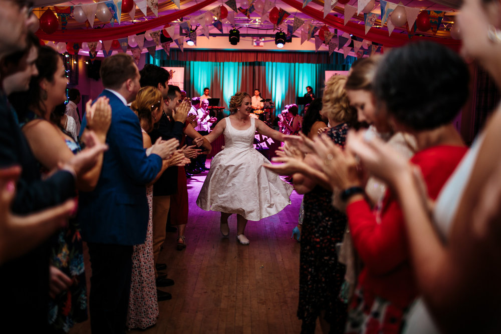 Bride ceilidh dancing at her wedding in Lancashire