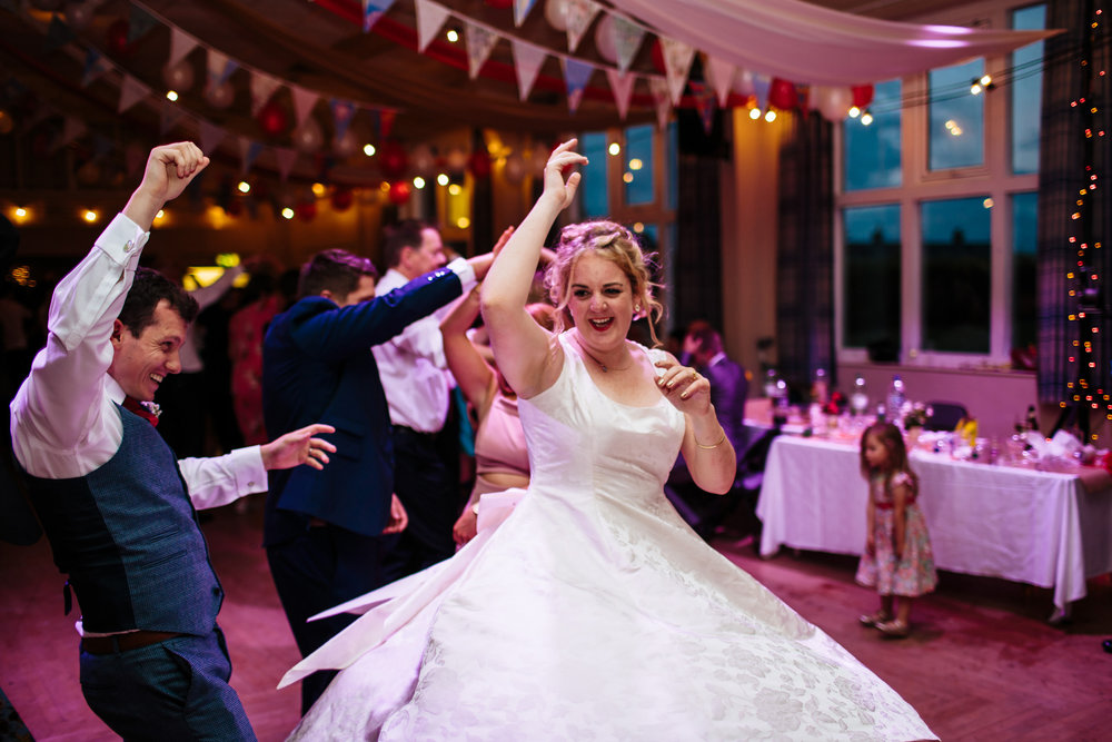Bride ceilidh dancing at her wedding