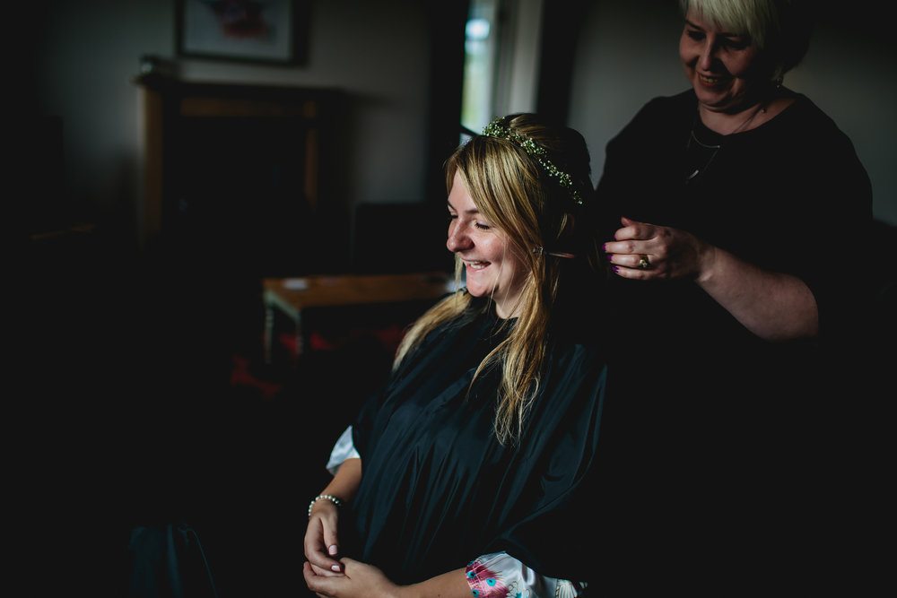Bride having her hair done on her wedding day