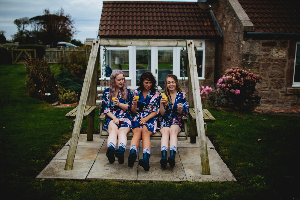 Bridesmaids on a swing drinking champagne at Cow Shed Crail