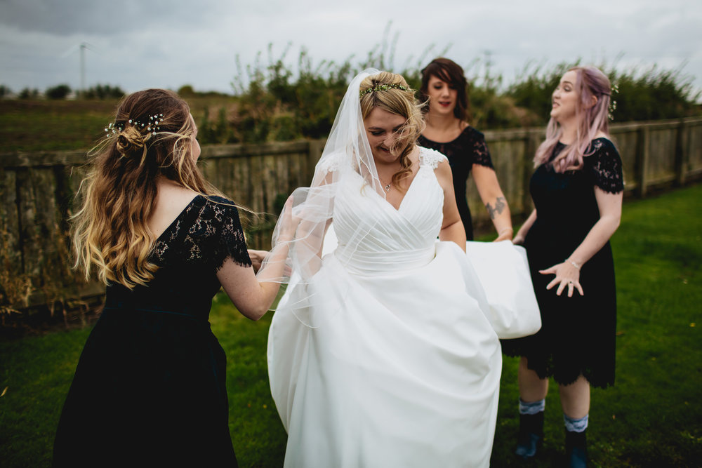 Bridesmaids helping with the wedding dress in Scotland