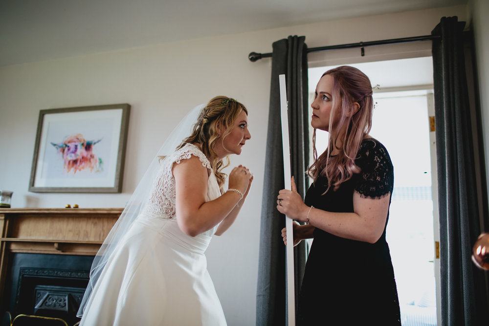 Bride checking herself in a mirror at a Scottish wedding