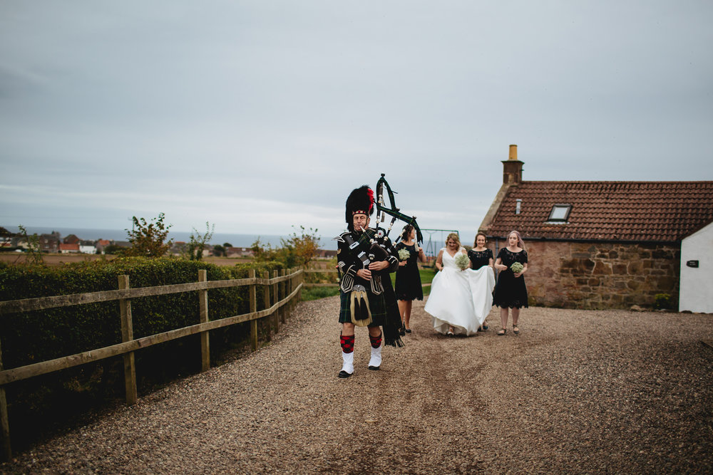 Piper and bride at a Cow Shed Crail wedding