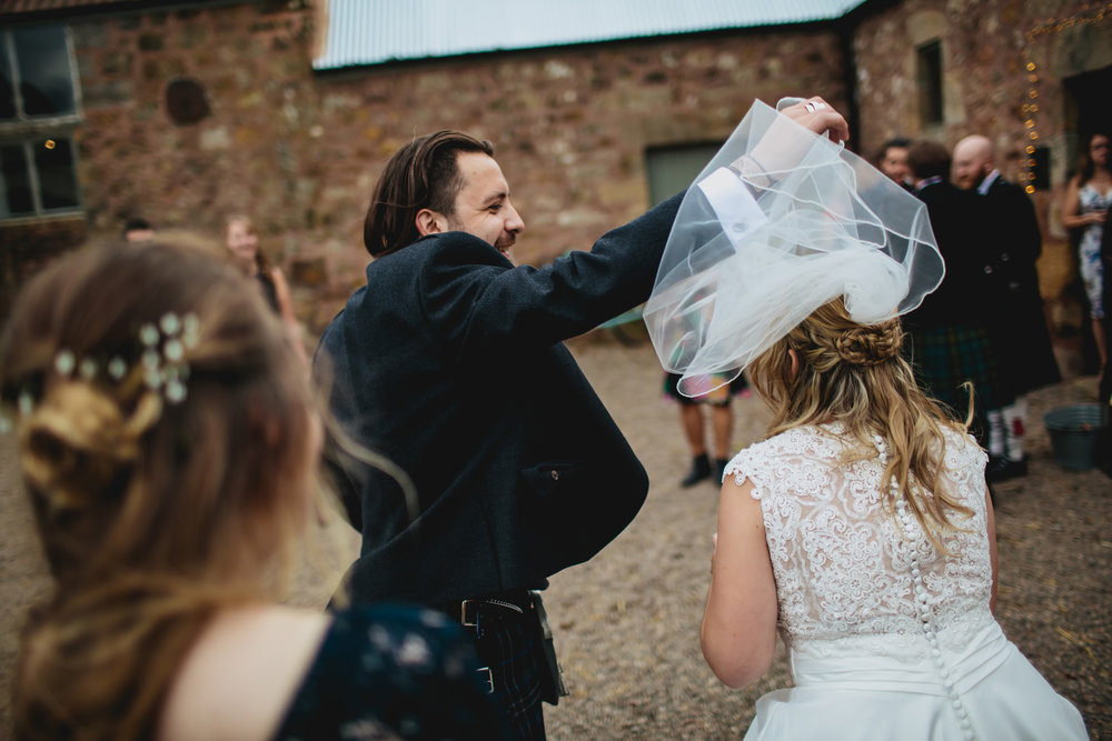 Bride has trouble with her windy veil in Scotland
