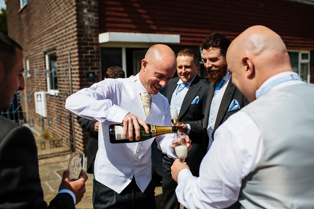 Groom pours champagne at his wedding in Lancashire