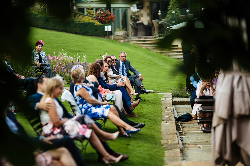 Wedding guests sitting on benches in Lancashire