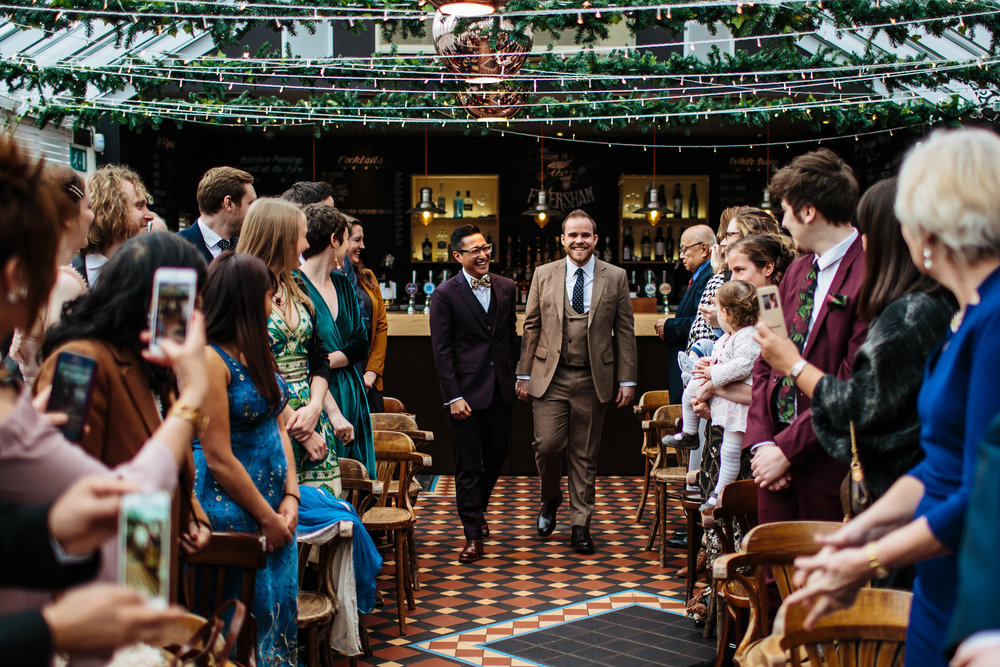 Grooms walk down the aisle at a gay wedding in Leeds