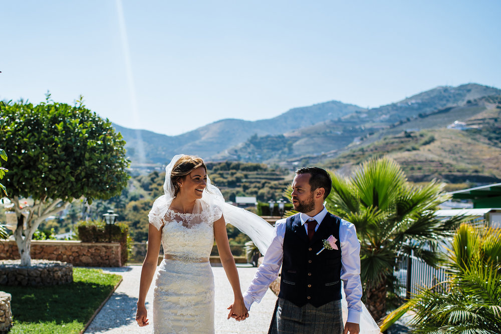 Bride and groom holding hands at Cortijo Maria Luisa Nerja Spain