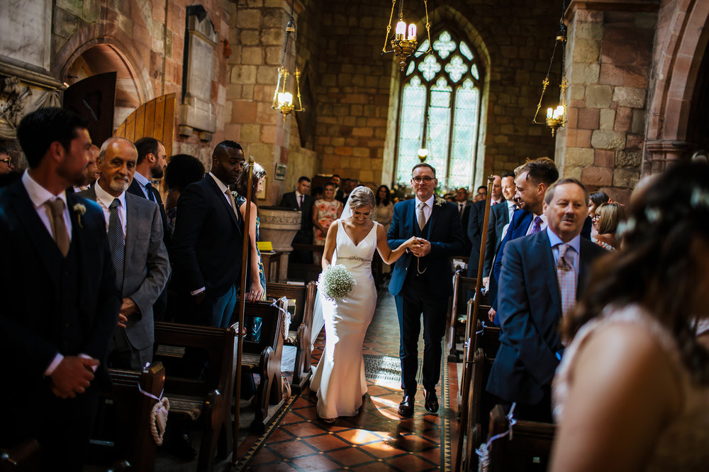Bride and father walk down the aisle in the church