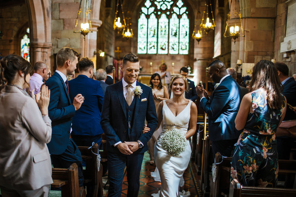 Bride and groom walk down the aisle at a Shropshire wedding