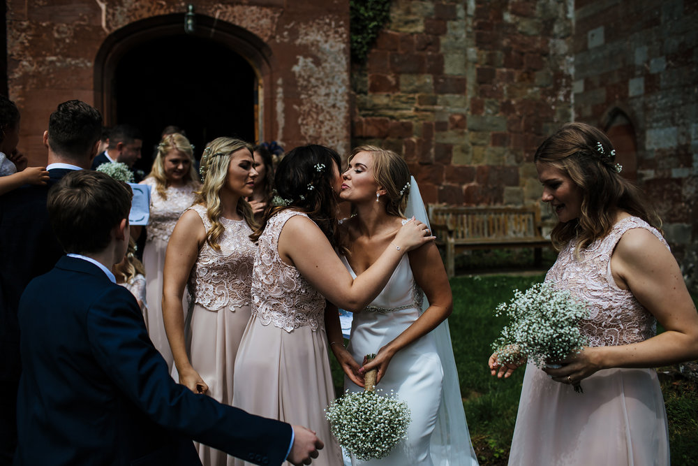 Bride kissing bridesmaid at a wedding in Shropshire
