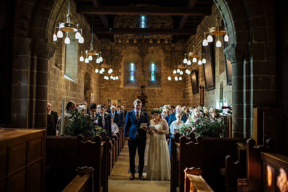 Bride and groom singing hymns in church at their wedding