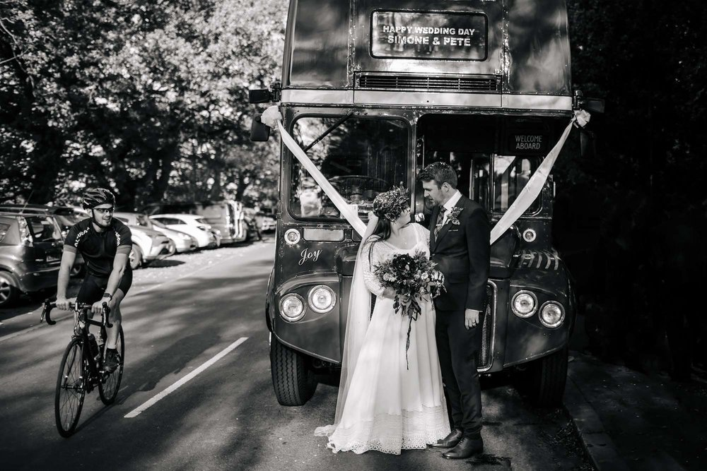 Bride and groom standing in front of their wedding bus in Leeds