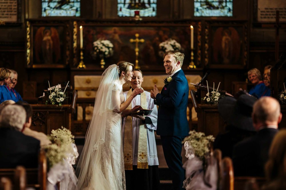 Bride and groom laughing during their church wedding ceremony