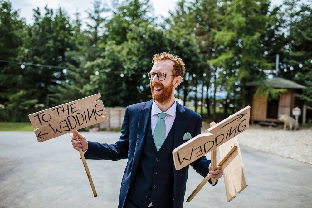 Groom with wedding signs in his hands