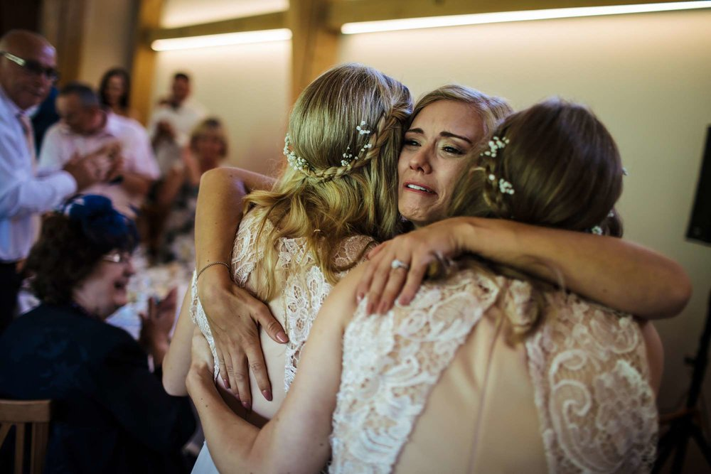 Bride in tears at her wedding with bridesmaids
