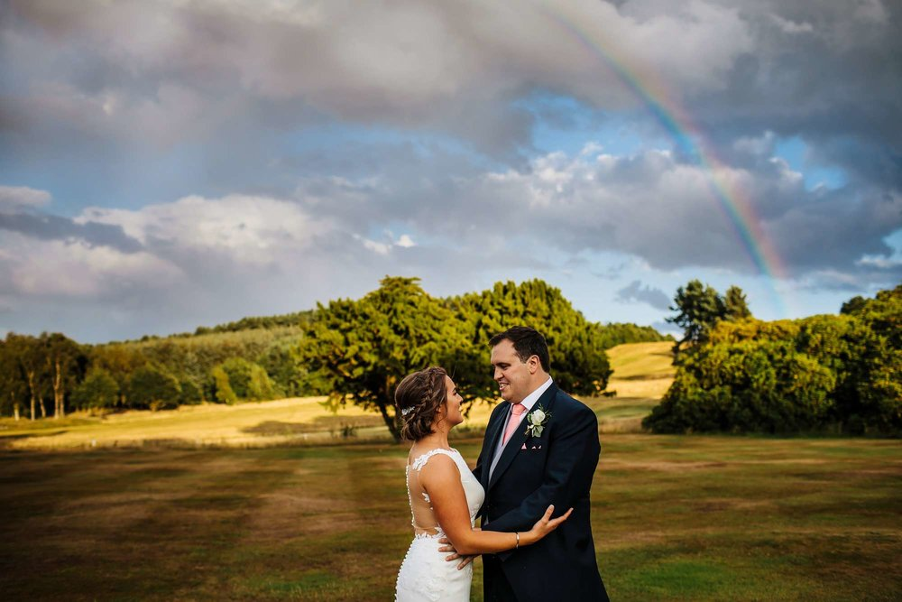 Bride and groom portrait with a rainbow in the background