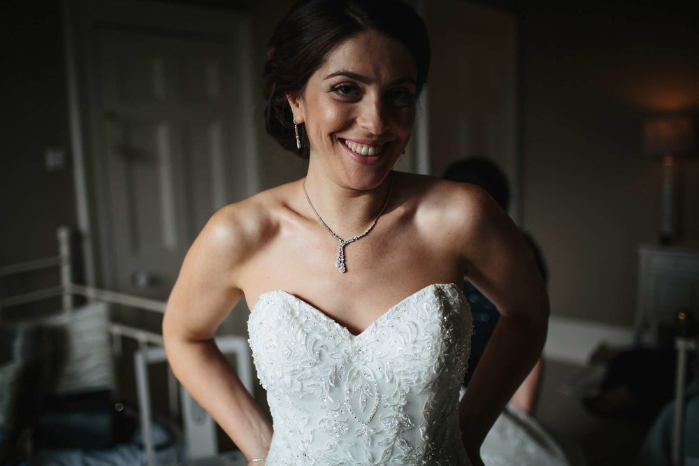 Bride smiling in her wedding dress during prep