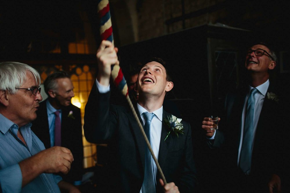 Groom ringing church bells at his wedding
