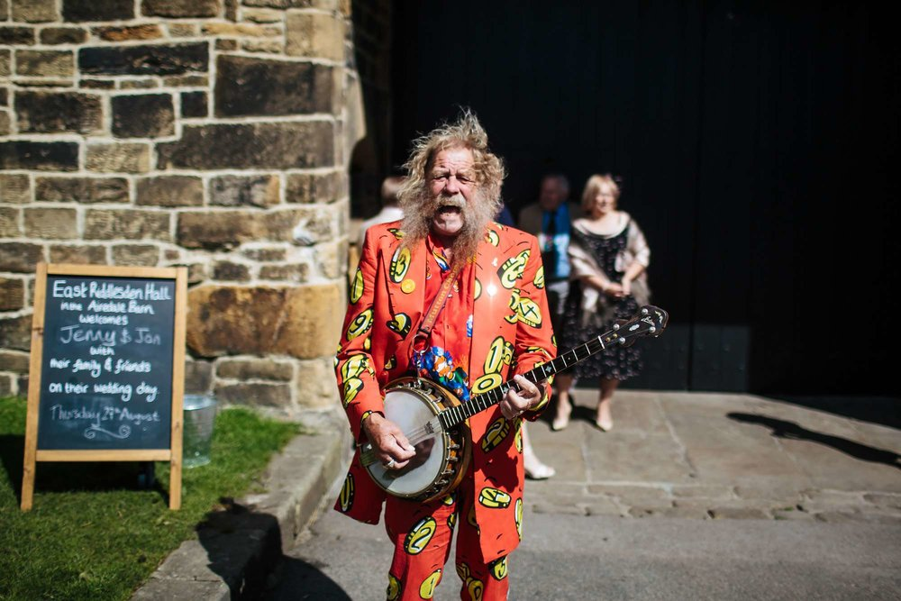 Bearded man playing the banjo in a bright red suit at a wedding