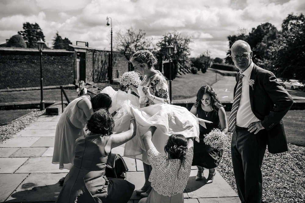 Bride has her wedding dress sorted by her bridesmaids as dad looks on