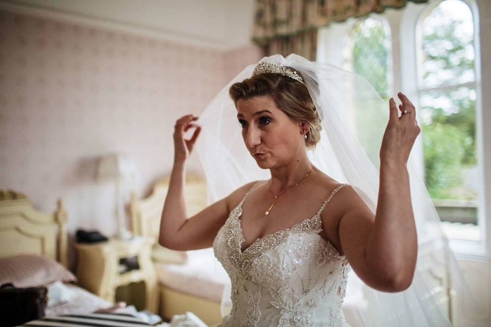 Bride adjusting her veil before her wedding