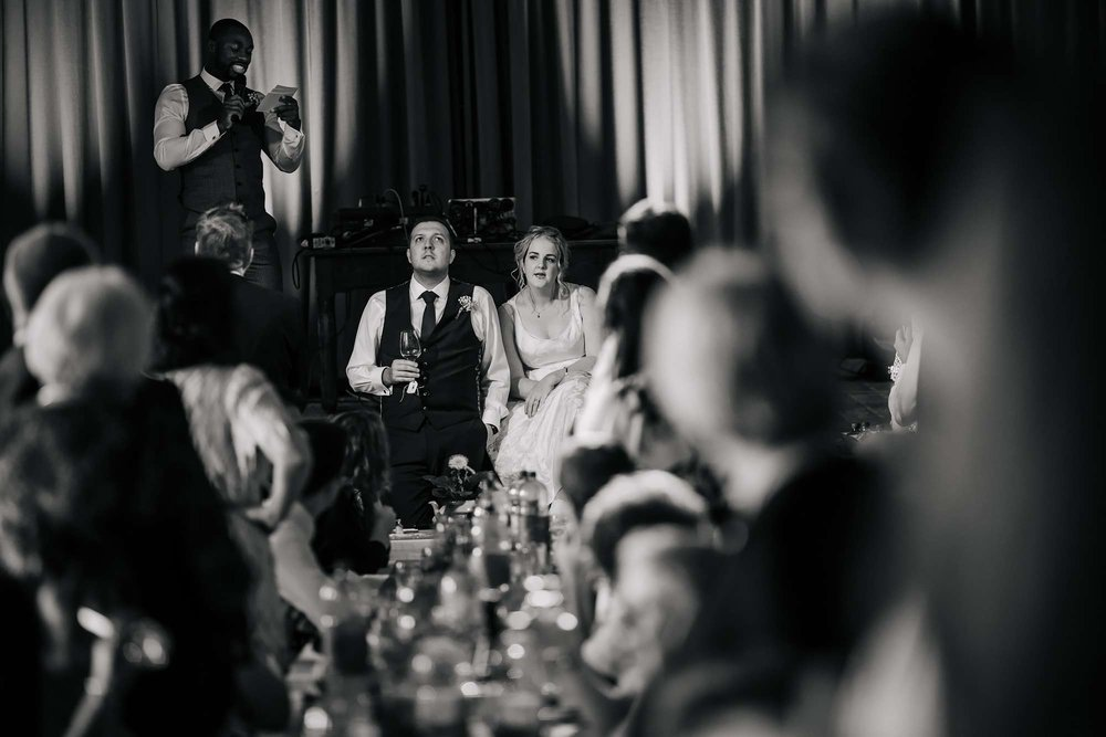 Bride and groom listen to the DJ talking down the microphone