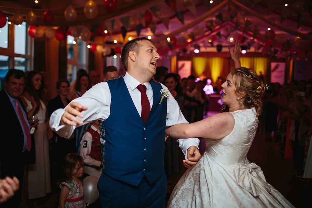 Bride and groom ceilidh dancing at their wedding in Yorkshire