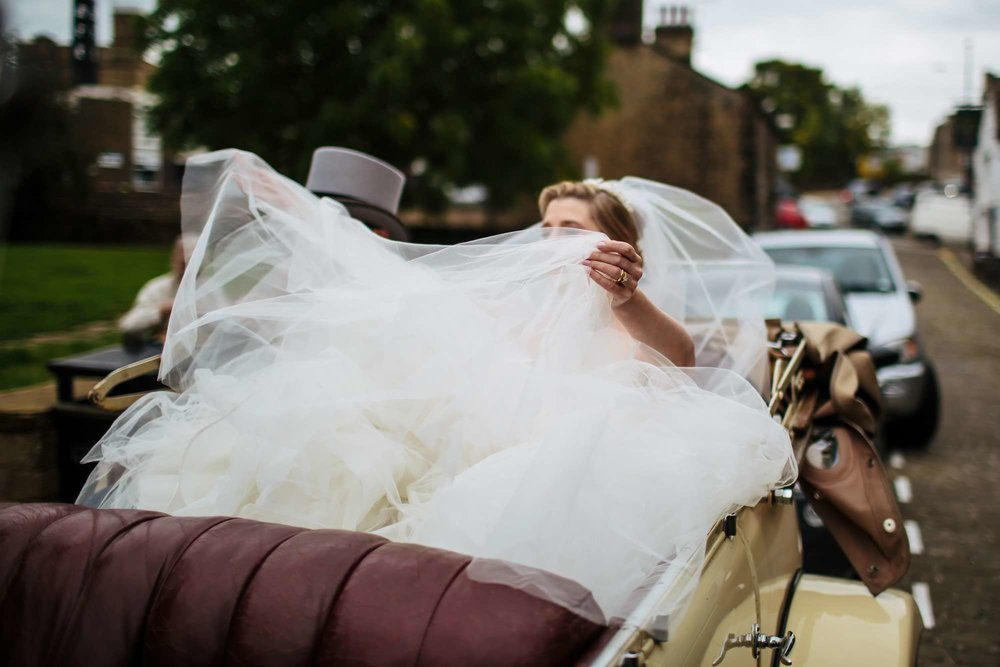 Bride adjusts her huge dress in her wedding car